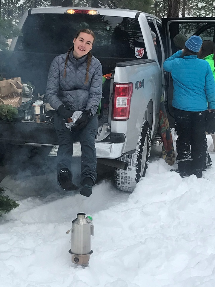 My daughter Kathryn warming her wet feet and drying her socks above the Kelly Kettle after finding the perfect Christmas tree.