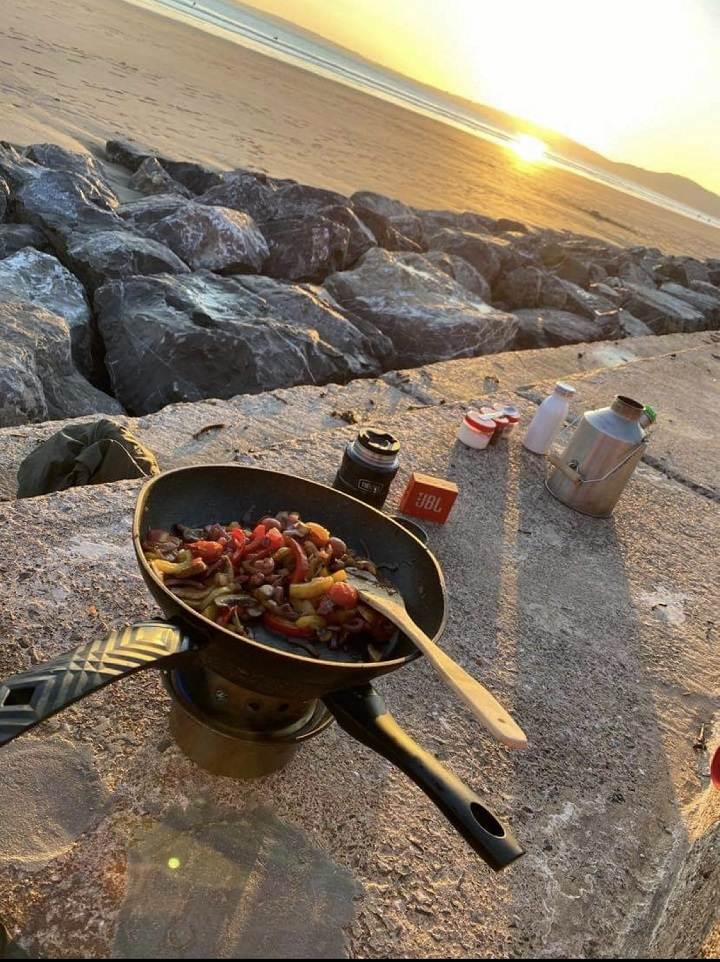 Cooking salmon with vegetables and rice on the hobo stove